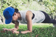 Young woman exercising workout fitness doing planking outside on. Grass  in summer park Stock Photos