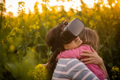 Young woman experience with virtual reality. Hugging her daughter with love. Royalty Free Stock Image
