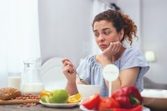Young woman experiencing lack of appetite. Lack of appetite. Young woman sitting at a breakfast table holding a spoon and looking disheartened while trying to Royalty Free Stock Photo