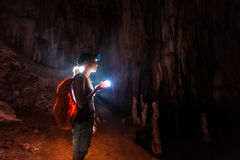 Young woman explores cave Stock Photo