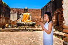 Young woman is exploring the ancient ruins of a buddhist temple Royalty Free Stock Photography