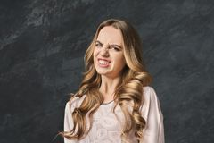 Young woman expressing disgust, grimacing. Young woman expressing disgust, feeling bad smell, grimacing at black studio background Royalty Free Stock Image