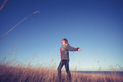 Young woman expressing freedom in field at sunset Royalty Free Stock Images