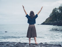 Young woman expressing freedom by sea Royalty Free Stock Image
