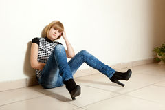 Young woman expressing sadness. Young woman sitting alone and expressing sadness Royalty Free Stock Photos