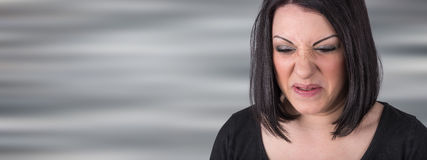 Young woman with an expression of disgust. On blurred background Stock Photography