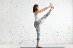 Young woman in Extended Hand to Big Toe pose, profile. Young attractive smiling woman practicing yoga, standing in Utthita Hasta Padangustasana exercise stock image