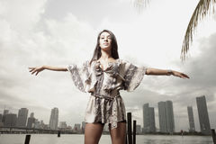 Young woman extending her arms. Beautiful young woman with her arms extended and the city in the background Stock Photography