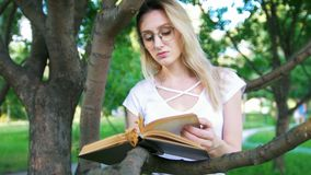 Young woman in eyeglasses eaning on a tree branch and reading a book in the park. Close up stock footage