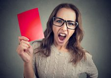Screaming woman with red card. Young woman in eyeglasses holding red paper and screaming angrily at camera on gray Stock Photography