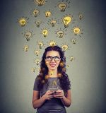 Woman with smarpthone developing ideas. Young woman in eyeglasses holding smarpthone has plenty of successful ideas Stock Photography