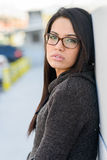 Young woman with eyeglasses in urban background Stock Photography