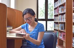Young woman in eyeglasses for vision corrective reading literature book. Preparing for exam stock image