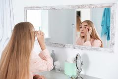 Young woman with eyelash loss problem looking in mirror royalty free stock photos