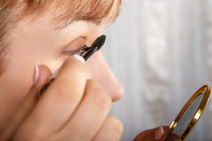 Young woman with eyeliner for her eyelashes Royalty Free Stock Photography