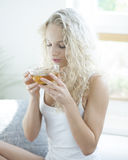 Young woman with eyes closed enjoying herbal tea in house stock image