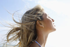 Young Woman With Eyes Closed Enjoying Sunlight. Side view closeup of young woman with eyes closed enjoying sunlight against sky at beach Stock Image