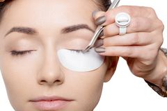 Young woman with eyes closed having a cosmetic procedure with the pincers on her eyelashes royalty free stock images