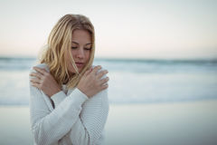 Young woman with eyes closed hugging self at beach. During dusk Royalty Free Stock Photos