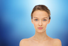 Young woman face with bare shoulders over blue Royalty Free Stock Photography
