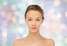 Young woman face with bare shoulders over lights Stock Photos