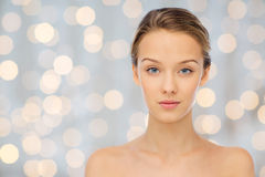 Young woman face with bare shoulders over lights Stock Images