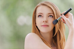 Young woman face brush handles Stock Images