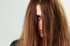 Young woman face covered with hair. Closeup portrait of a young woman face covered with hair Stock Photography