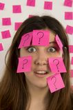 Young woman face covered in question mark stickies. Young woman  with nose ring  with pink sticky notes and question mark thinking about decision making Royalty Free Stock Images