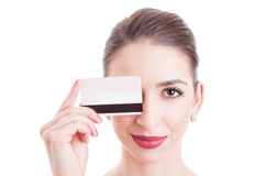 Young woman face with eye covered by credit debit card Royalty Free Stock Image