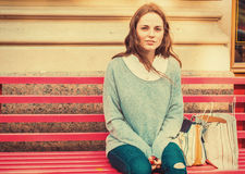 Young woman with face with freckles is siting on a bench. Outdoor picture in full man's length. Royalty Free Stock Photography