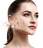 Young woman face made from crumbly powder. Over white background stock photo