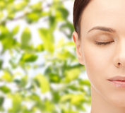 Young woman face over green leaves background Royalty Free Stock Photo