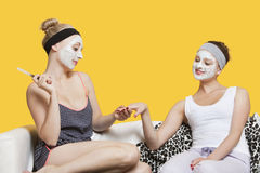 Young woman with face pack filing friend's nails while sitting on sofa over yellow background Royalty Free Stock Photos