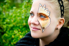 Young woman with face painting. With green bushes in the background Royalty Free Stock Image