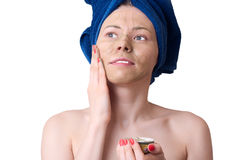 Young woman with facial clay mask. On a white background Stock Photos