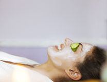 Young woman with a facial mask and cucumber on her face. Young happy woman with a facial mask and cucumber on her face royalty free stock photos