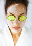 Young woman with a facial mask and cucumber on her face Stock Photography