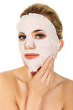 Young woman with facial mask Stock Images