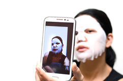 Young woman with facial mask selfie Stock Images
