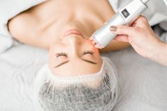 Woman during a facial massage. Young woman during a facial massage with professional tool at the medical center stock photo