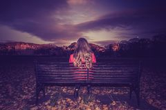 Young woman facing away seated on a bench royalty free stock photography
