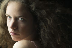 Young Woman with Fair Skin, Blue Eyes and Light Brown Curly Hair in Dramatic Lighting Stock Photos