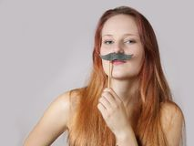 Young woman with fake moustache. Young woman holding a fake moustache on a stick to her face stock image
