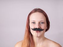 Young woman with fake moustache Royalty Free Stock Photography