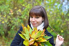 Young woman with fall leaves. Young woman with autumn orange leaves in forest stock photography
