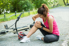 Young Woman Fallen From Bicycle Royalty Free Stock Image
