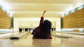 Young woman falls down while throws a bowling ball