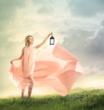 Young Woman on a Fantasy Hilltop. Young woman on a fantasy grassy hilltop with antique lamp royalty free stock image