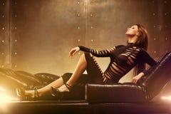 Young woman fashion. Young sexy woman lying on sofa Stock Image